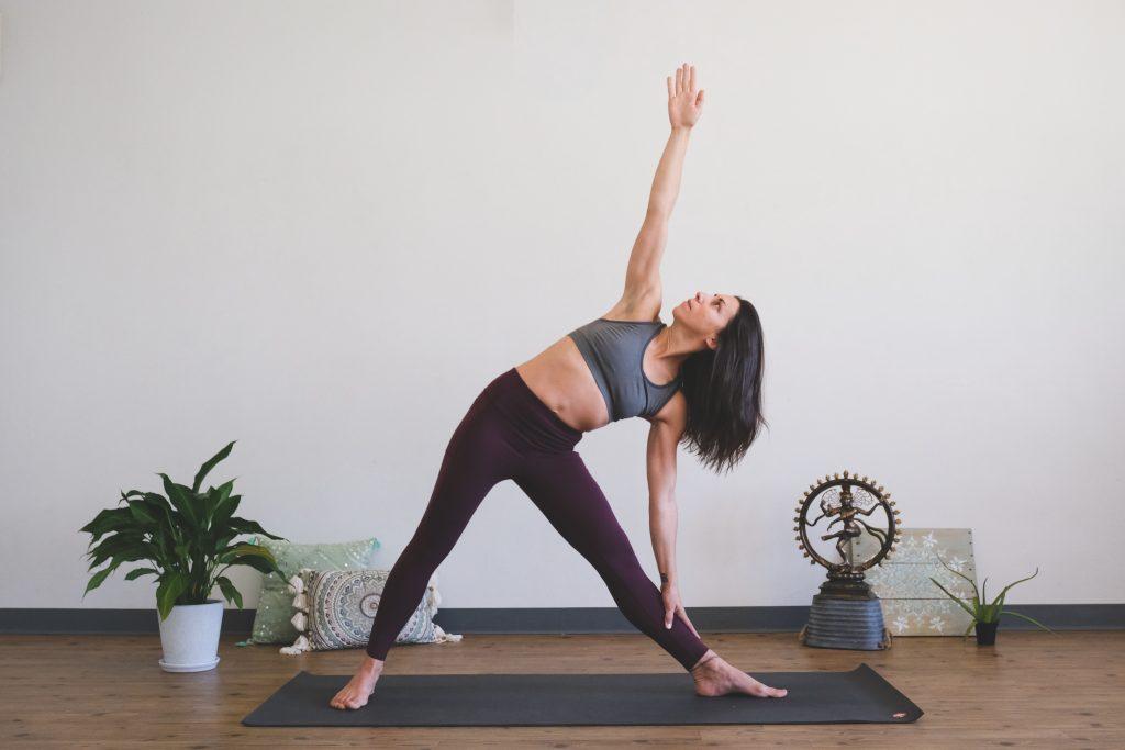 Peace Love And Yoga, a Hot Yoga Studio in Carlsbad California shares yoga myths and misconceptions; woman practicing yoga | woman in trikonasana