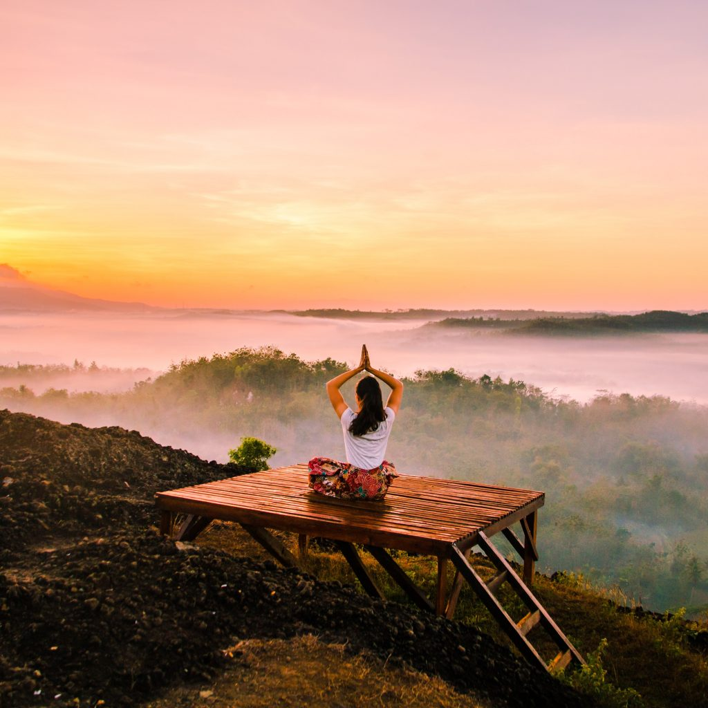 Peace Love And Yoga in Carlsbad California shares all the tips to help you decide if a yoga retreat is right for you; woman outdoors practicing yoga.