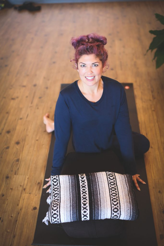 Erin Holmes from Peace Love And Yoga, shares a peaceful Restorative Yoga Flow; woman in a restorative yoga pose.