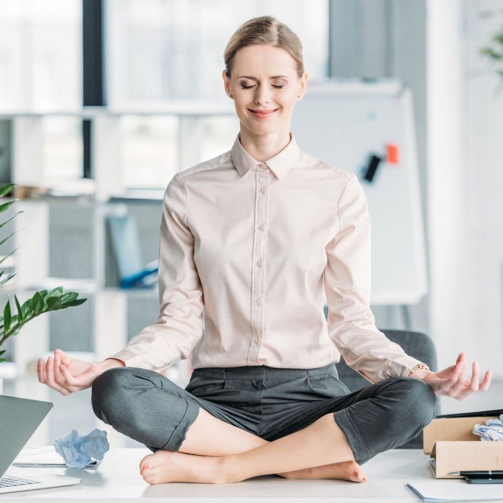 5 Easy Ways To Add Yoga To Your Life featured by Peace Love And Yoga A Hot Yoga Studio In Carlsbad California; woman doing yoga in her office.